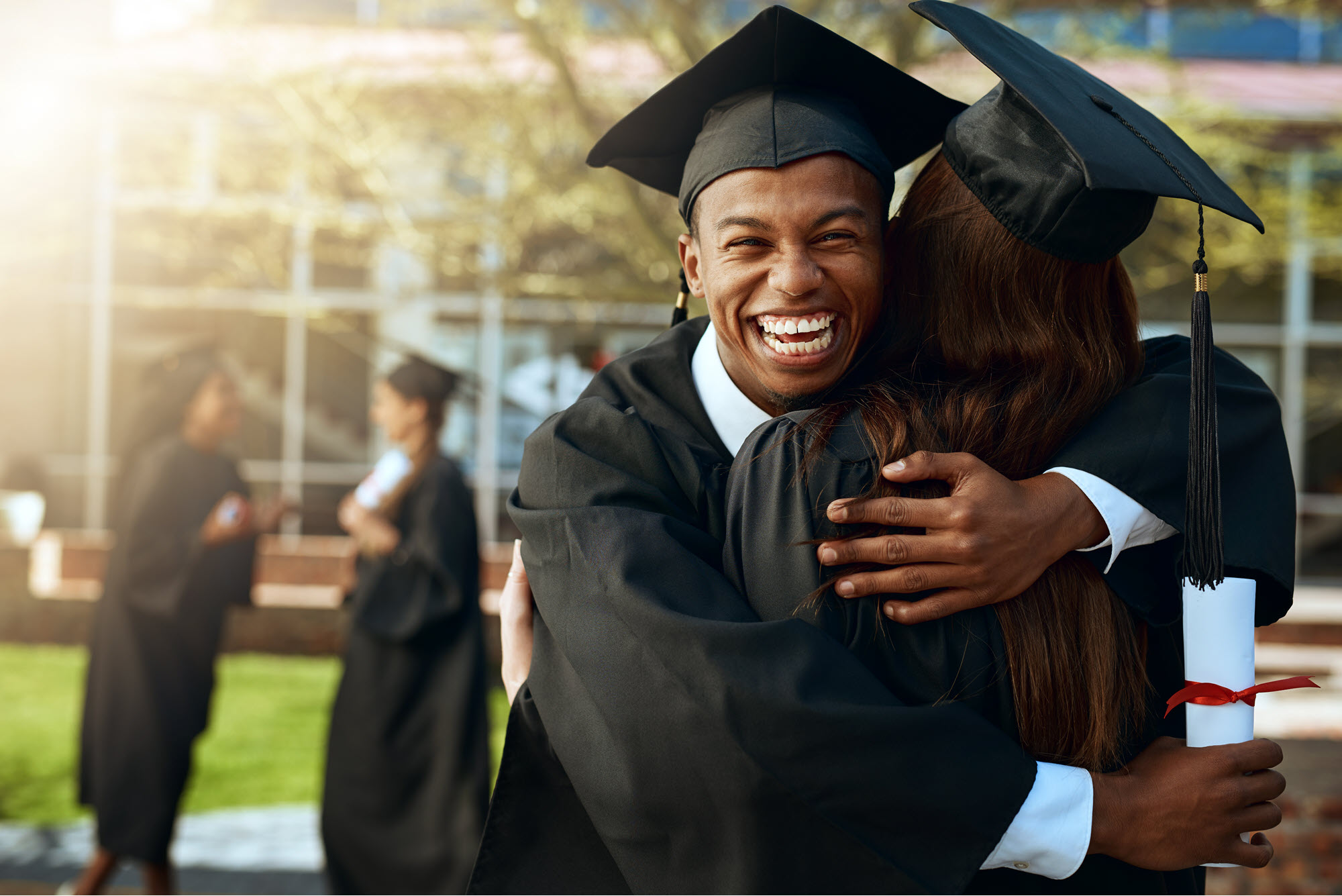 High school male graduate hugging another graduate