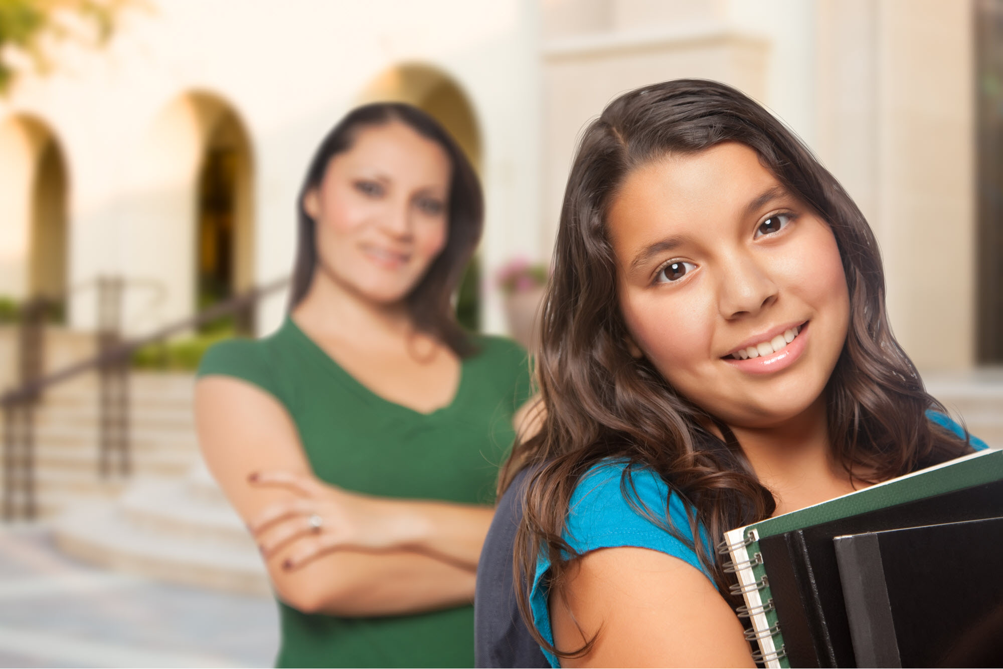 middle school girl holding books with mom in the background