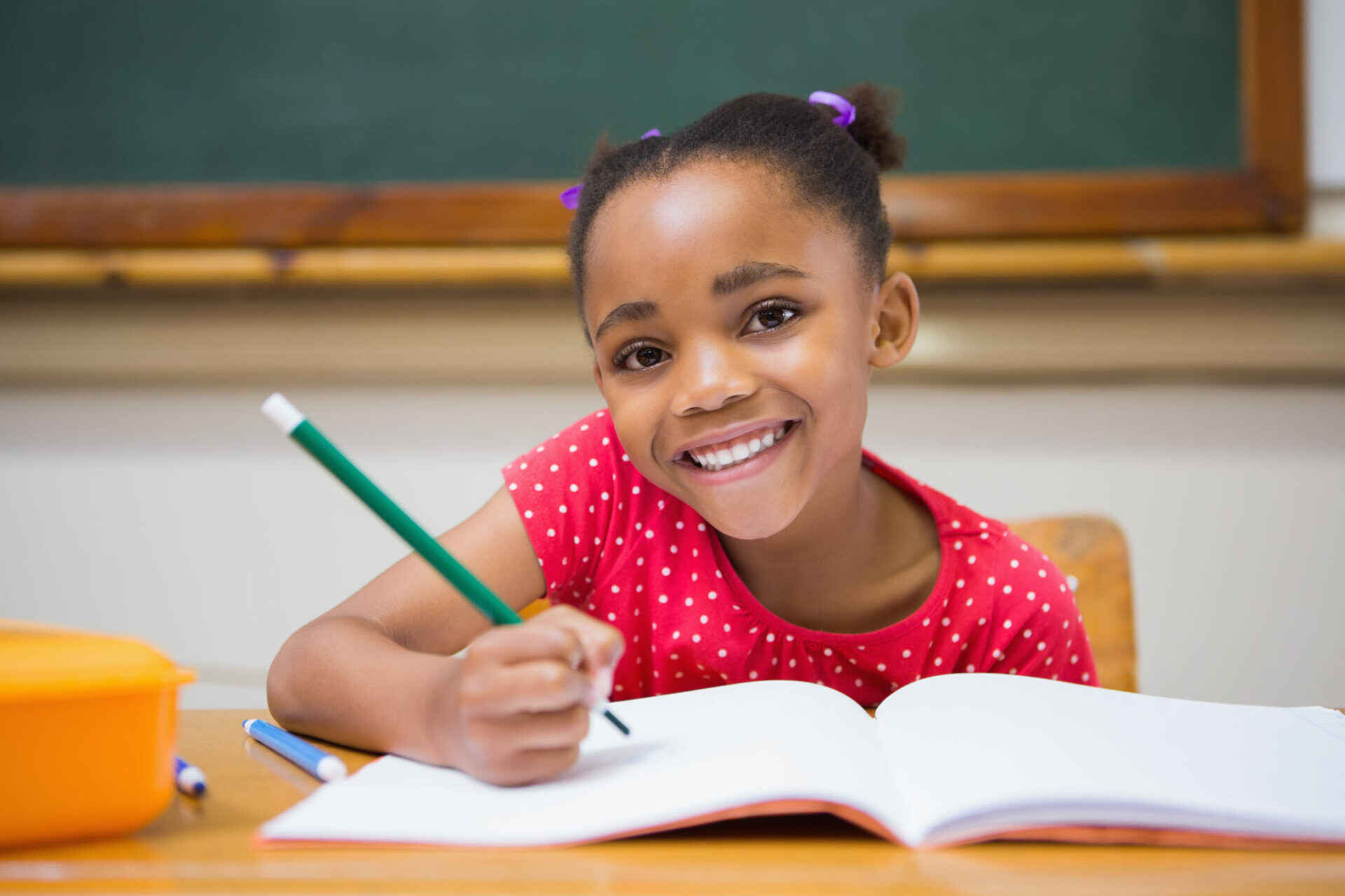 elementary school girl smiling holding a pencil