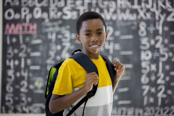 elementary school boy smiling while standing in front of the chalkboard