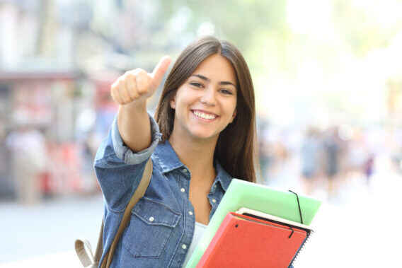 high school girl holding books giving a thumbs up