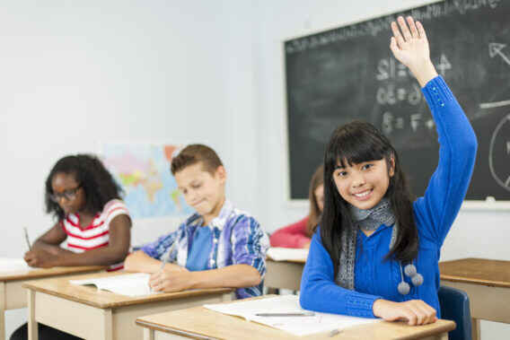 middle school girl smiling with hand raised