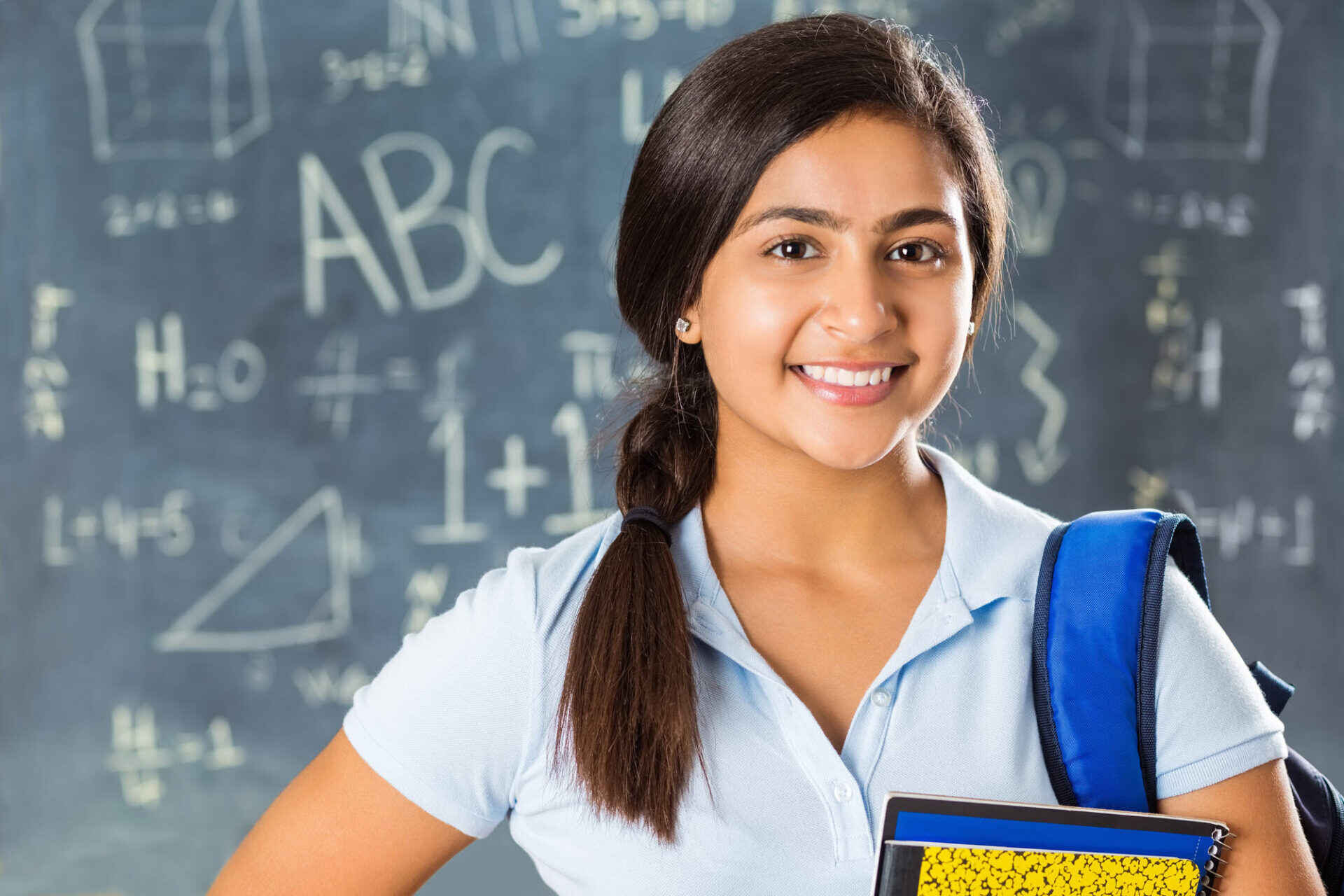 middle school girl smiling in front of a chalkboard